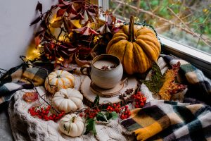 Cozy autumnal Pumpkin latte scene by the window with autumn leaves, pumpkins, knits and hot drink