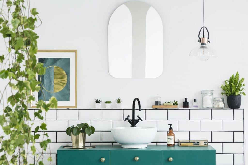 Mirror on white wall above green washbasin in bathroom interior