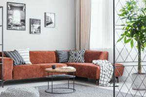 Pillows and blanket on brown velvet corner sofa in elegant living room interior