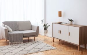 Living Room Interior Background With Comfortable Couch, Drawer And Plants