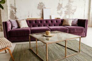 Purple velvet sofa with golden pillow in living room interior