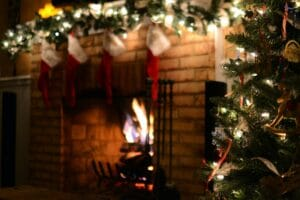A traditionally decorated Christmas tree in front of a fire place with a fire and decorated mantle